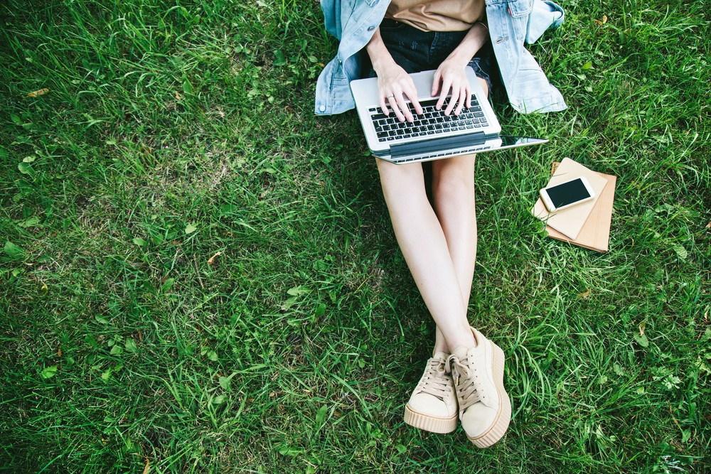 Kobieta z komputerem pracuje na trawie