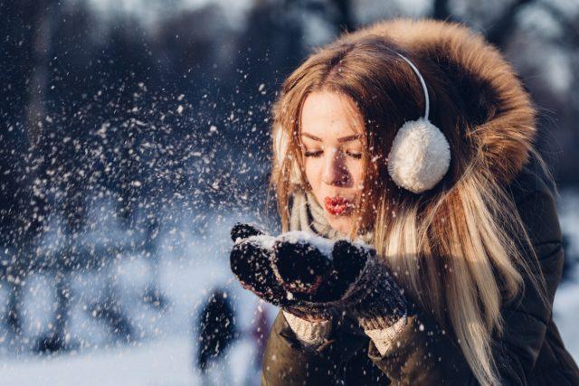 Kobieta zimą bawi się śniegiem