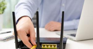 Mężczyzna wpina kabel do routera