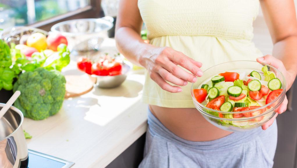 Kobieta w ciąży je warzywa