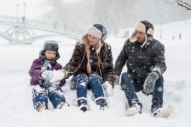 Kobieta mężczyzna i dziecko siedzący w głębokim śniegu