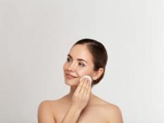 Kobieta oczyszczająca twarz mleczkiem do demakijażu