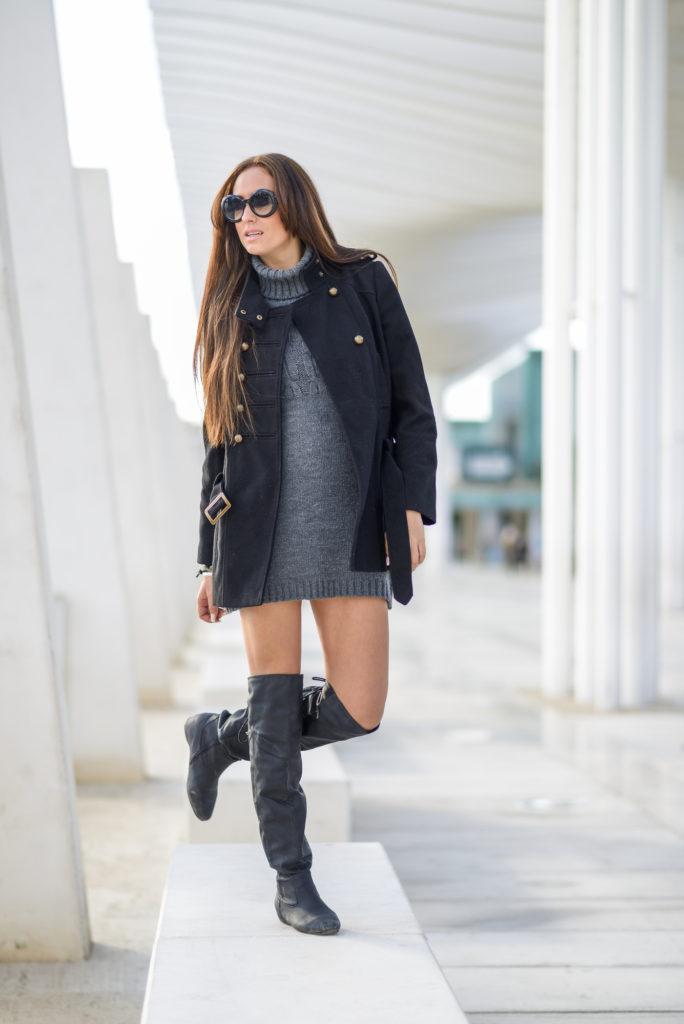 Młoda kobieta w czarnych kozakach za kolano szarym swetrze i czarnej kurtce