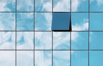 Okna wieżowca odbijające chmury