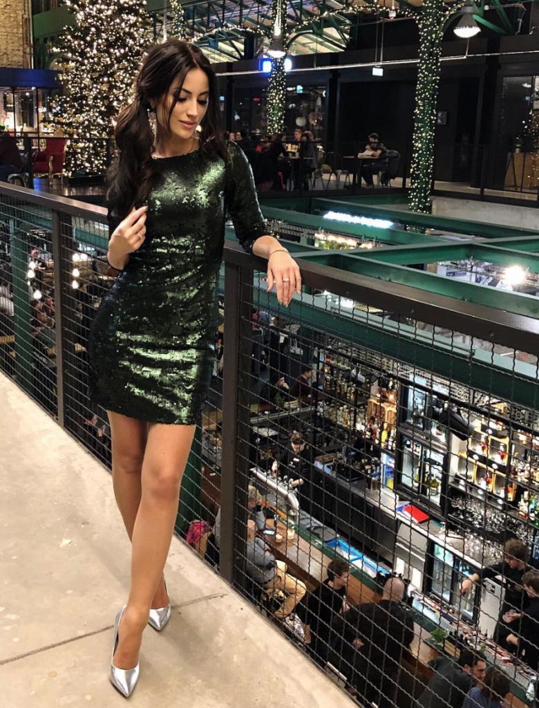 Kobieta w sukience na sylwestra i lustrzanych butach