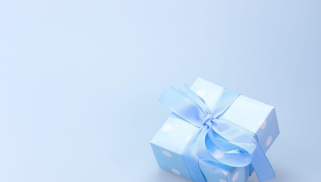 prezent zapakowany w niebieski papier z białymi kropkami i niebieską kokardą