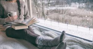 kobieta siedząca przy oknie i czytająca książkę zimą