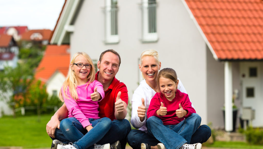 rodzina siedząca przed domem