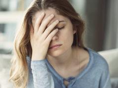 młoda smutna kobieta z ręką przy twarzy