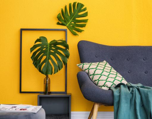 salon w żółtym kolorze zielony kwiat szara kanapa