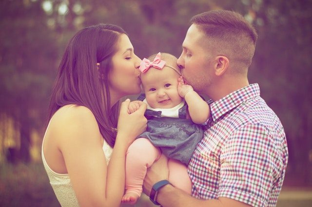 dwójka rodziców ze słodką dziewczynką na rękach