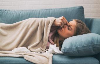 kobieta z bólem zatok leżąca na łóżku pod kocem