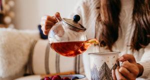 kobieta nalewająca herbatę do kubka
