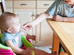małe dziecko w foteliku do karmienia