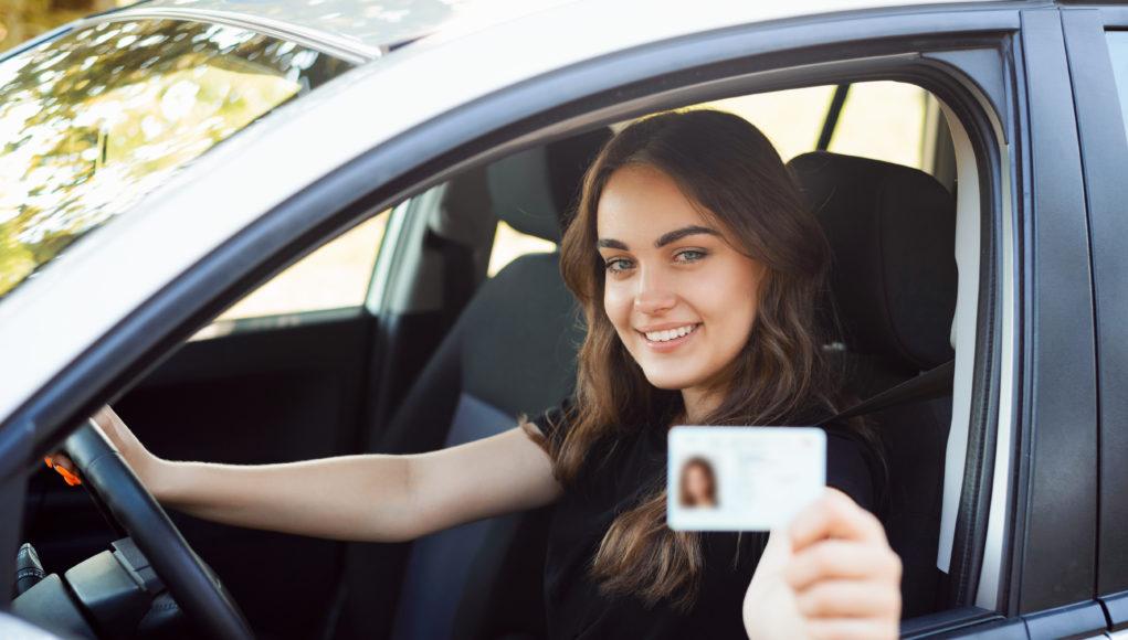szczęśliwa dziewczyna za kierownicą z prawem jazdy