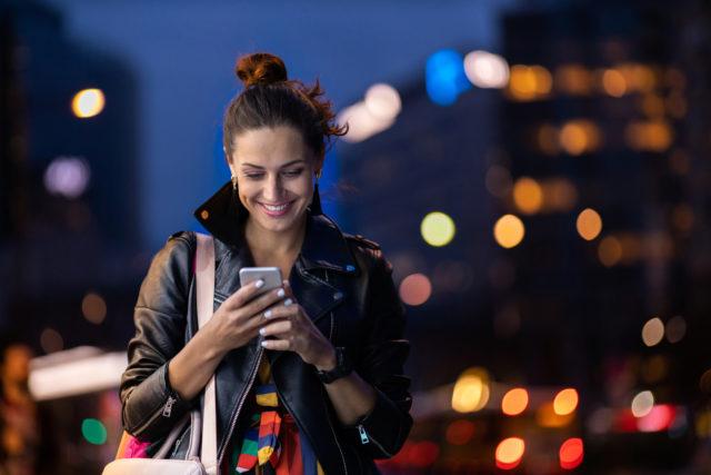 młoda dziewczyna ze smartfonem w ręku na tle miasta wieczorem