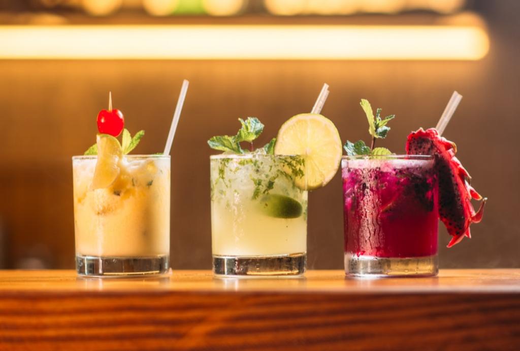 trzy kolorowe drinki w szklankach