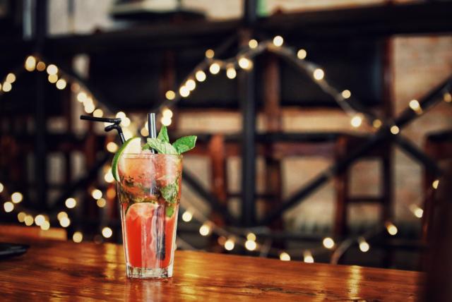 drink w szklance na drewnianym stole w tle lampki