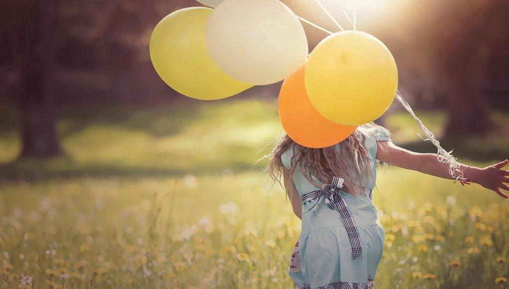 dziewczynka biegnąca z balonami