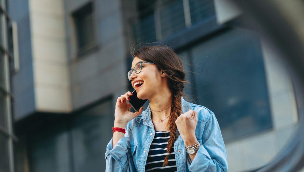 młoda kobieta rozmawiająca na ulicy przez smartfona