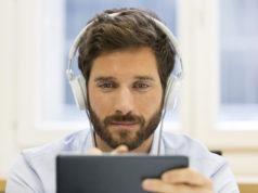 młody mężczyzna pracujący na tablecie w słuchawkach