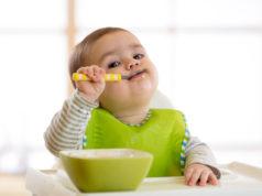 niemowlę jedzące łyżeczką posiłek z miski
