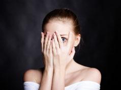 przestraszona kobieta zakrywająca twarz dłońmi