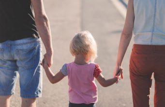 rodzice prowadzący dziewczynkę za rękę