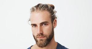 zbliżenie na przystojnego mężczyznę blondyna z brodą i kucykiem