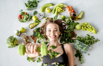 dziewczyna z hantlami na tle zielonych warzyw i owoców