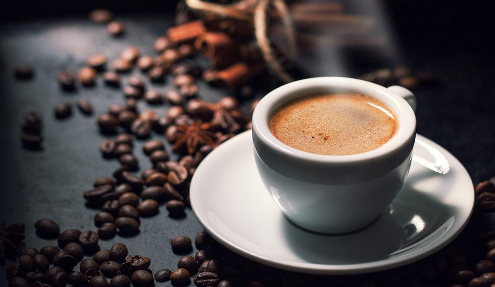 filiżanka espresso na tle rozsypanej kawy