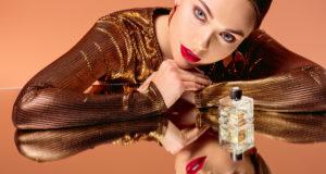 piękna kobieta w złotej sukience na złotym tle z perfumami