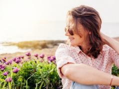 kobieta w różowej koszuli w groszki na tle kwiatów
