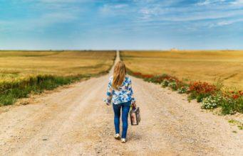 kobieta z walizką idąca wiejską drogą