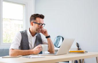 zadowolony młody biznesmen przed ekranem laptopa