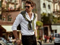 przystojny mężczyzna w koszuli i narzuconym na ramiona swetrze