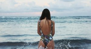 kobieta w stroju kąpielowym wchodząca do morza