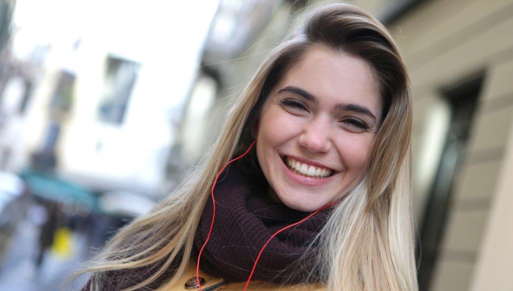 wesoła kobieta w kurtce i szaliku ze słuchawkami przewodowymi w uszach