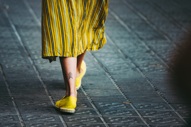 zbliżenie na kobiece nogi na ulicy w żółtej spódnicy z żółtymi espadrylami na stopach stylizacja casual