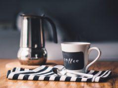 makinetka i kubek kawy na drewnianym stole