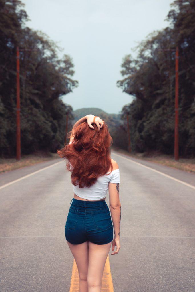 kobieta w szortach typu hot pants stojąca na drodze