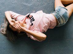 kobieta na podłodze w różowej bluzce i szortach
