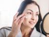 kobieta przed lustrem nakładająca krem na twarz