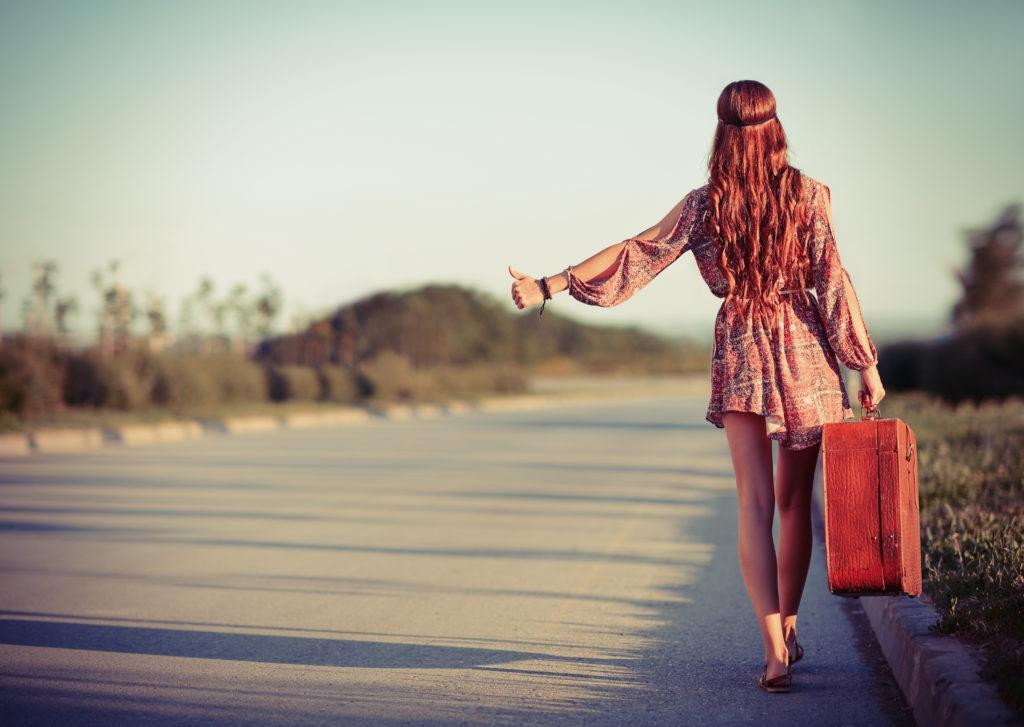 kobieta w stylu hippie łapiąca stopa na ulicy