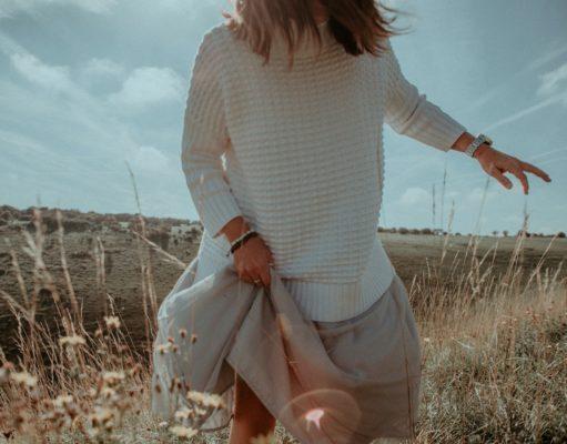 kobieta w swetrze spódnicy na łące