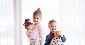 dwie dziewczynki noszące lalki w nosidełkach