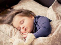 dziewczynka w wieku przedszkolnym śpiąca w pościeli