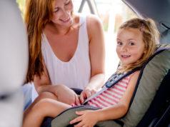 kobieta zapinająca córkę w foteliku samochodowym