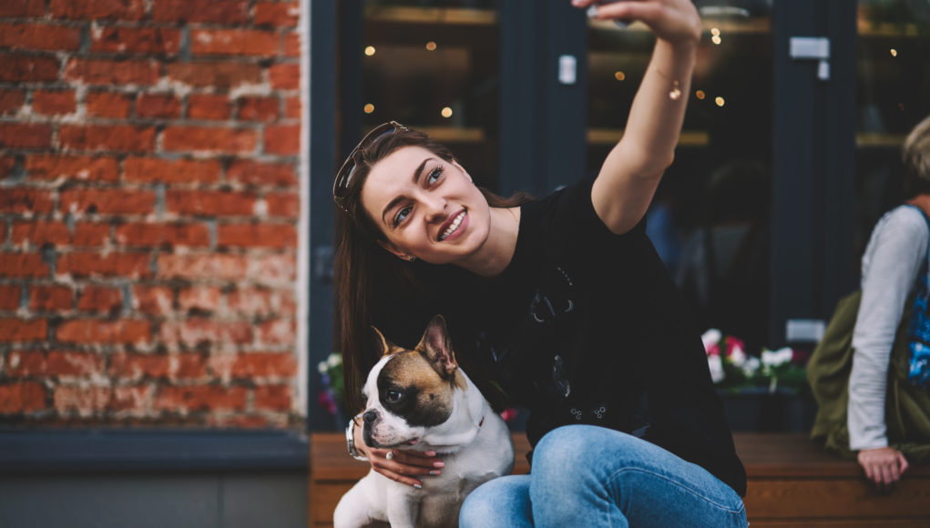młoda Francuzka robiąca sobie zdjęcie z psem