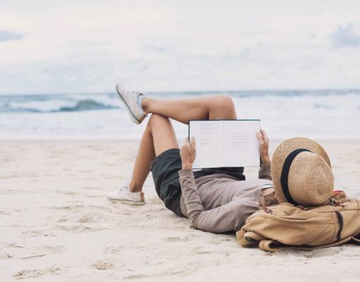 młoda kobieta czytająca na plaży
